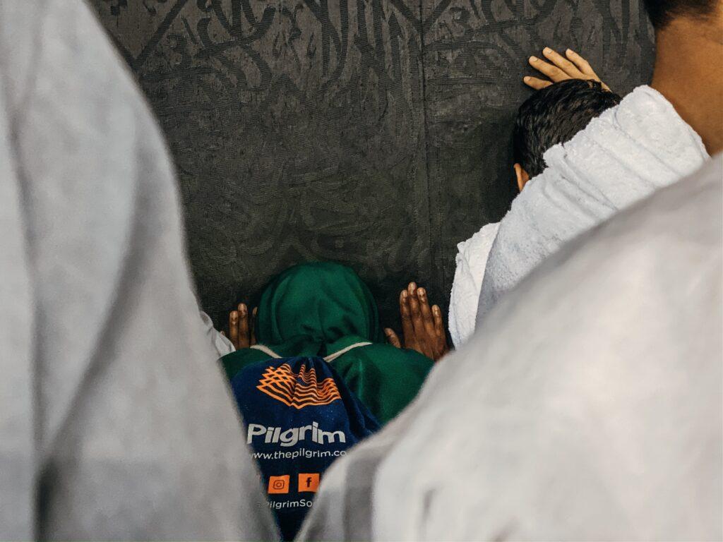 Muslim pilgrim placing forehead on the Kaaba